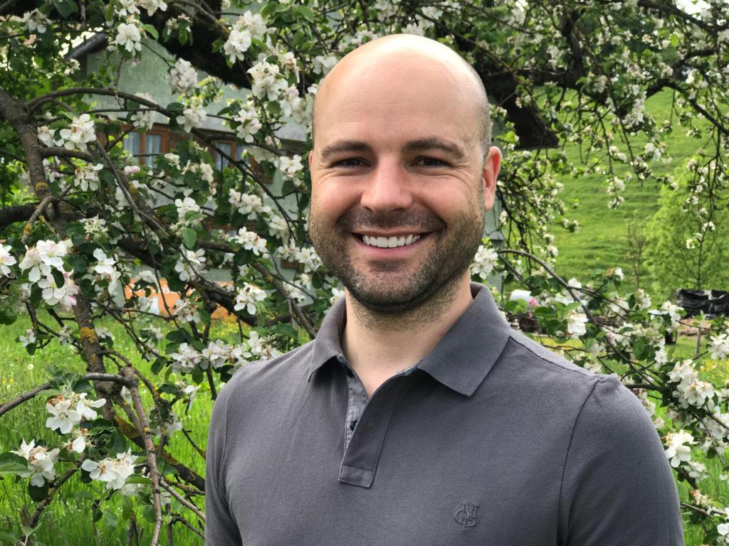 Portrait von Dr. Matthias Wucherer vor einem blühenden Apfelbaum im Allgäu